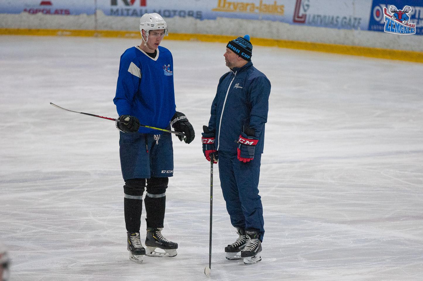 Gara auguma hokejists uz ledus sarunājas ar treneri.
