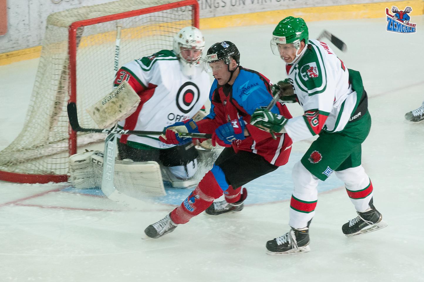 Zemgale/LLU uzbrucējs Ričards Bernhards #15 izslido starp vārtsargu Vadimu Miščukuku #31 un aizsargu Normundu Vībānu #28 spēlē LOC ledus hallē Liepājā 2017. gada 21. oktobrī.