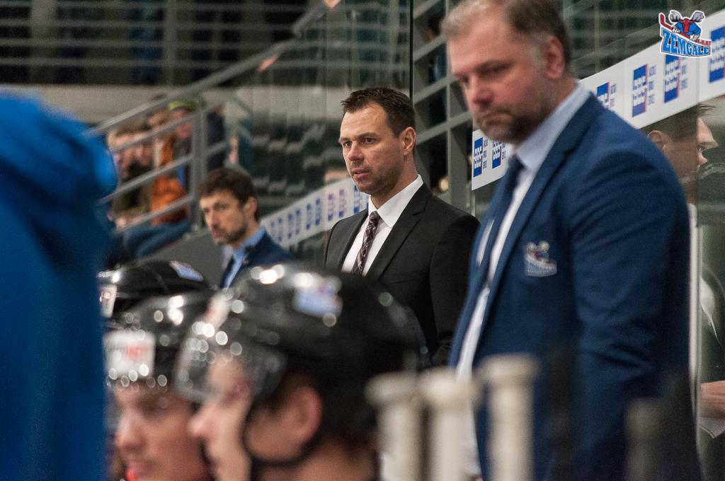 Hokeja treneris uzvalkā un šlipsē uz rezerves soliņa
