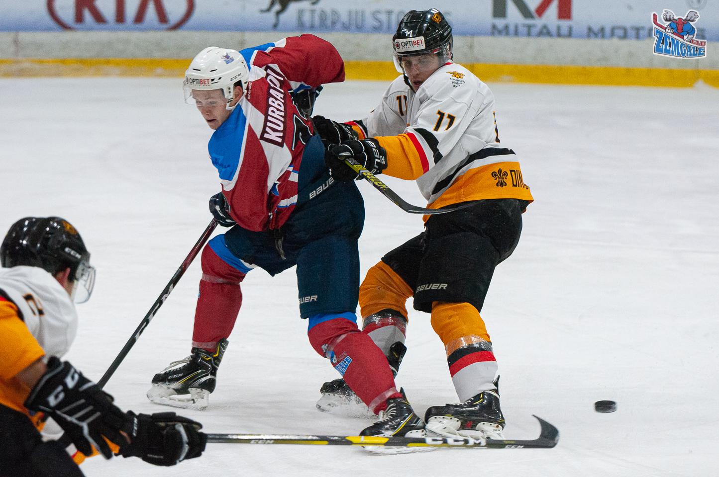 Viens hokejist grūž otru mugurā, kamēr cits spēlētājs raida prom ripu