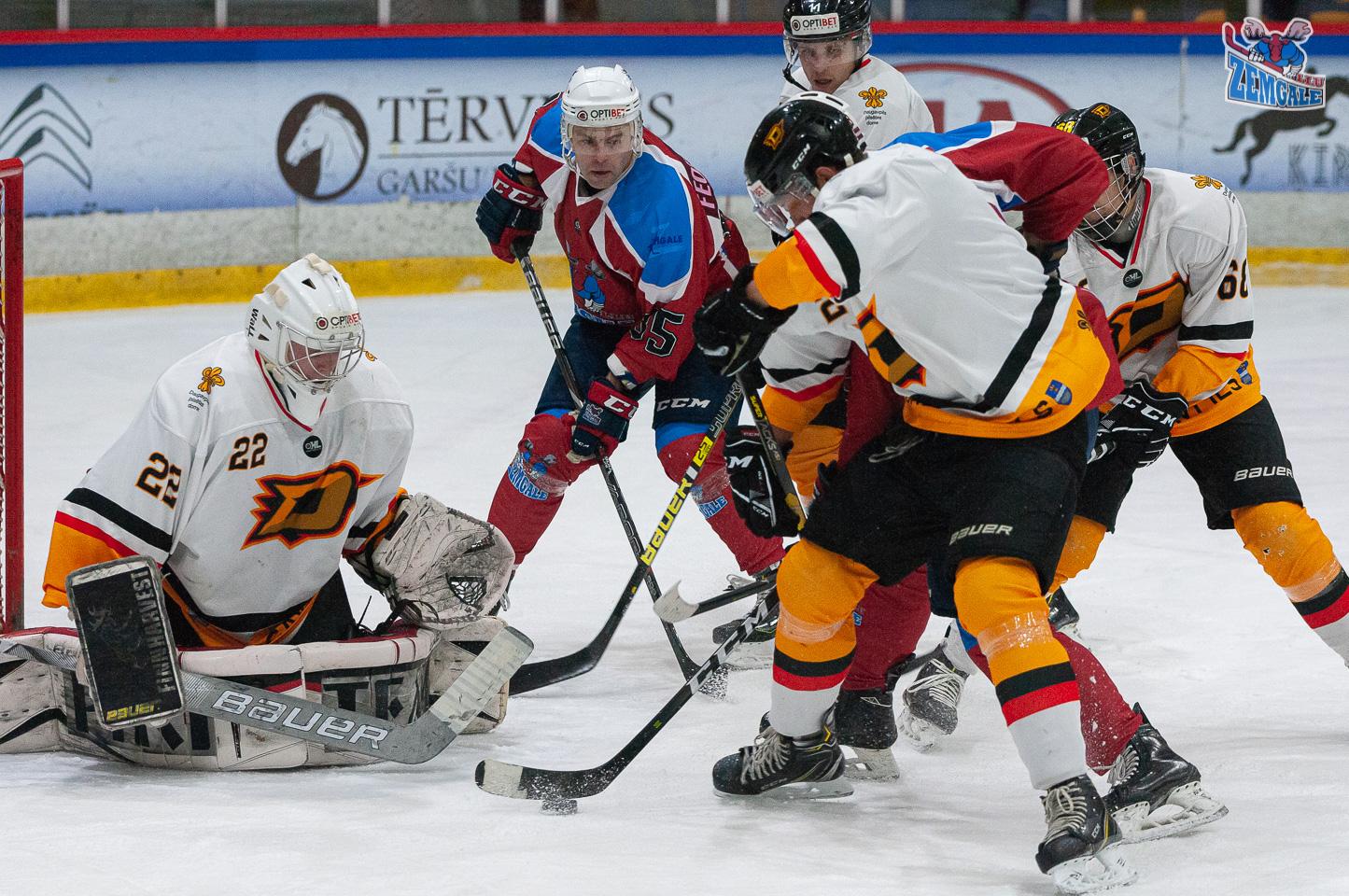 Vārtsargs un hokejisti cenšas neielaist ripu vārtos