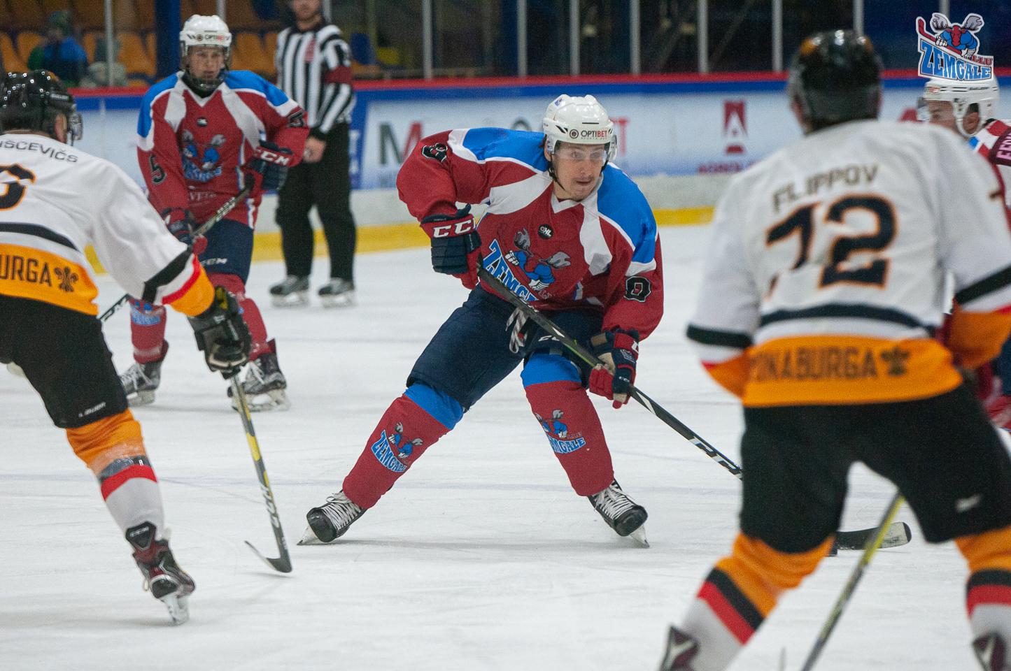 Hokejist mēģina izlidot caur diviem pretiniekiem