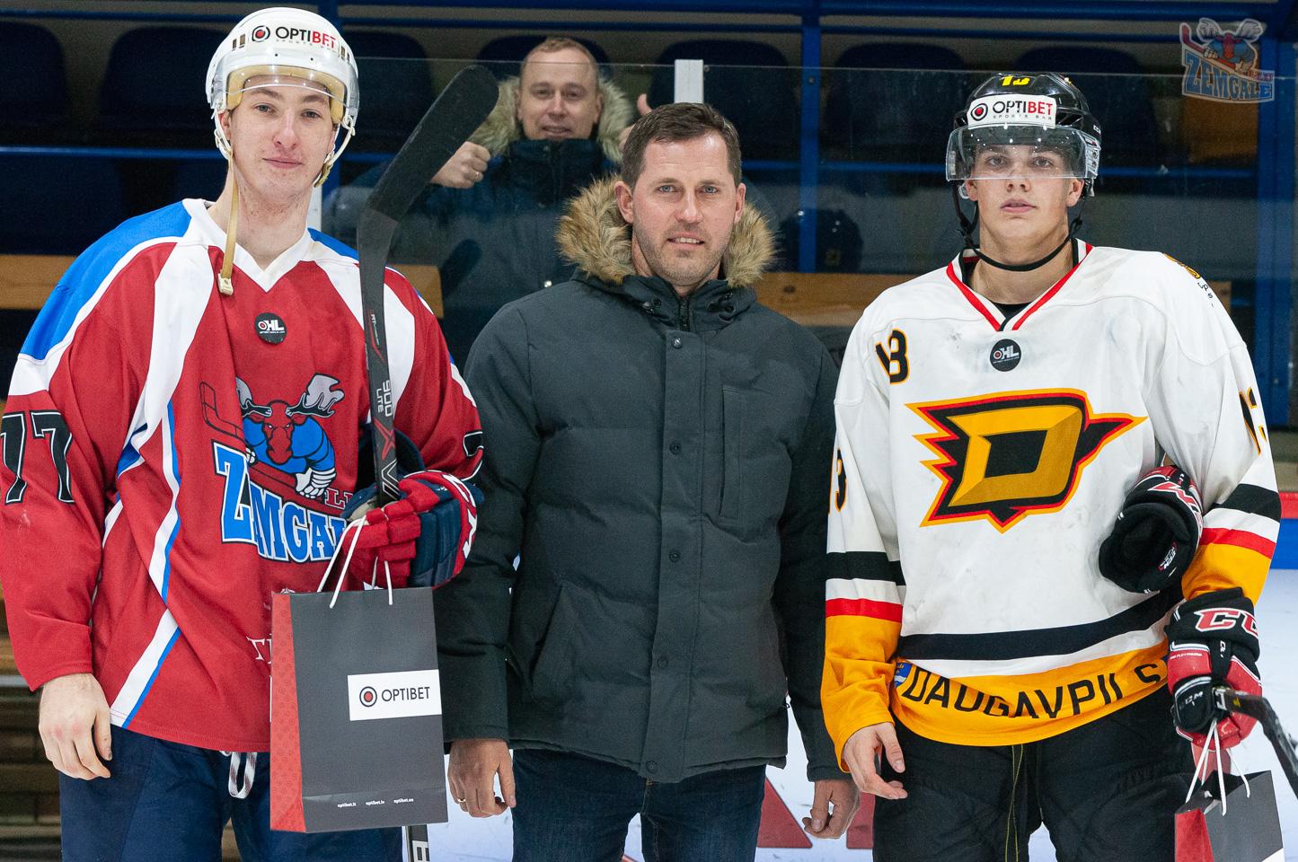 Divi hokejisti un vīrietis stāv priekšējā fonā ar maisiņiem