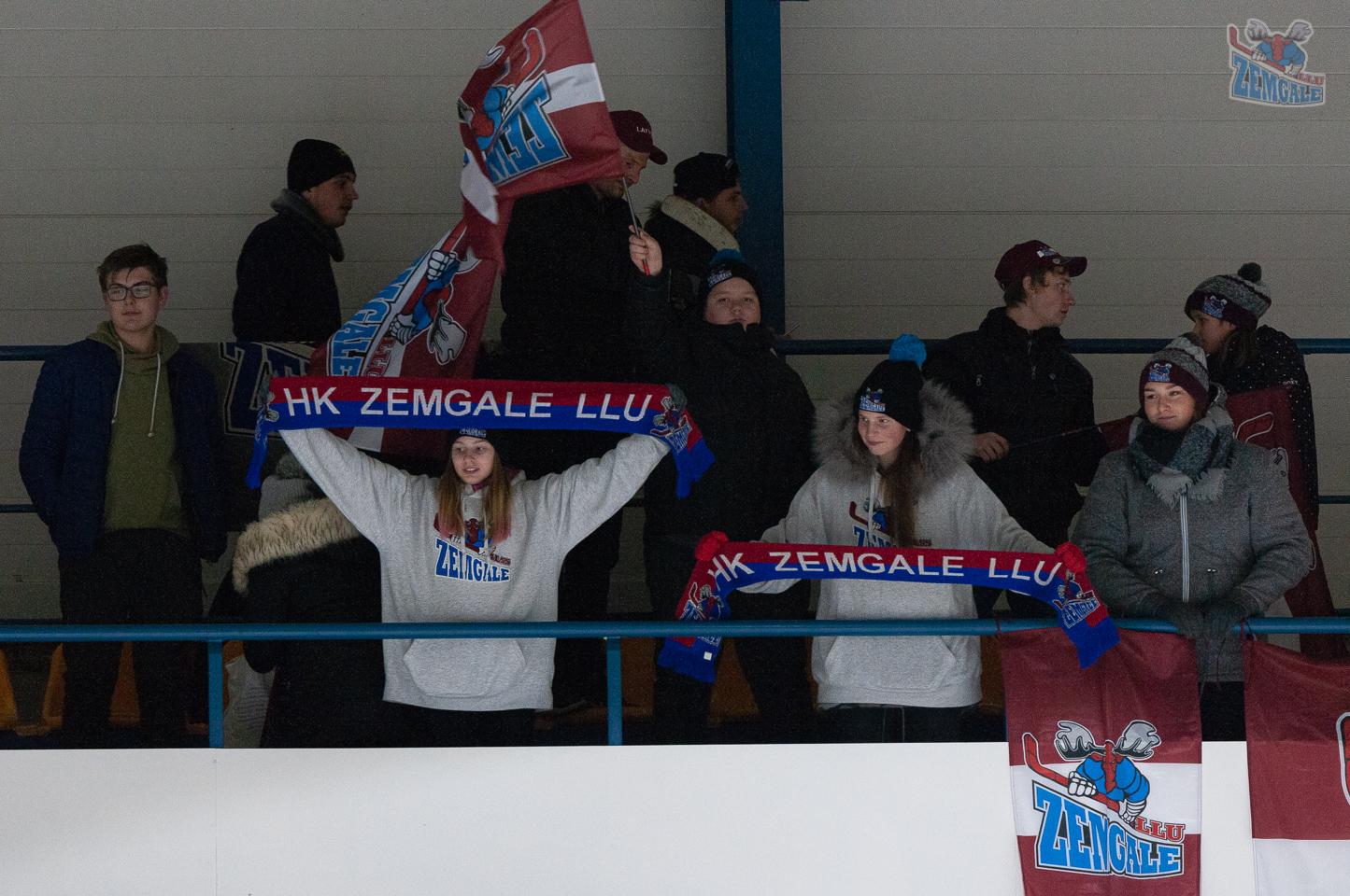 Jaunieši ar karogiem un šallēm stāv tribīnē
