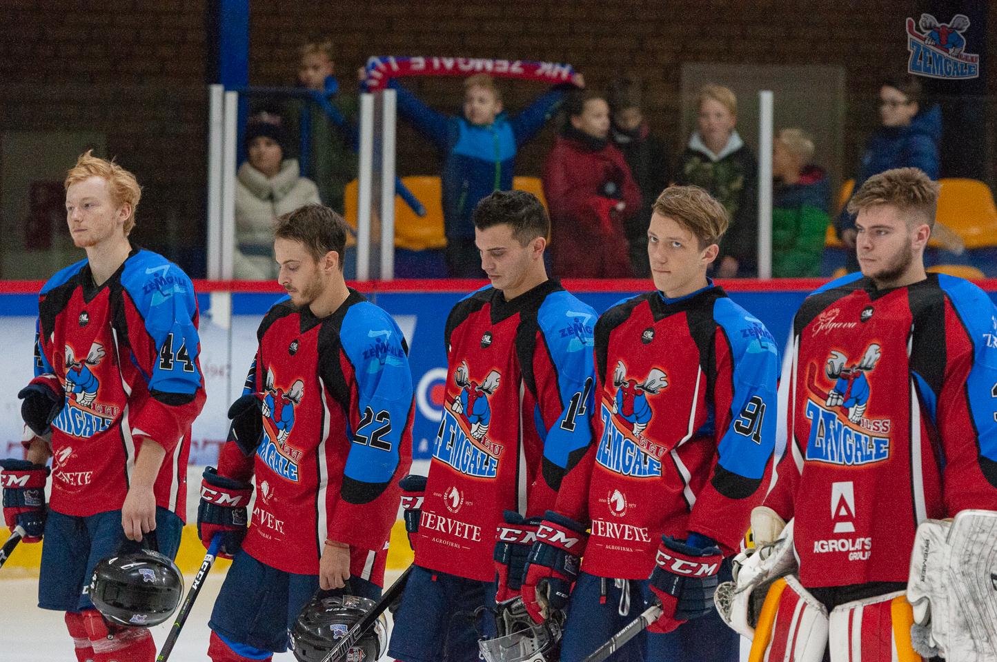 Hokeja komanda un tās mazie fani fonā