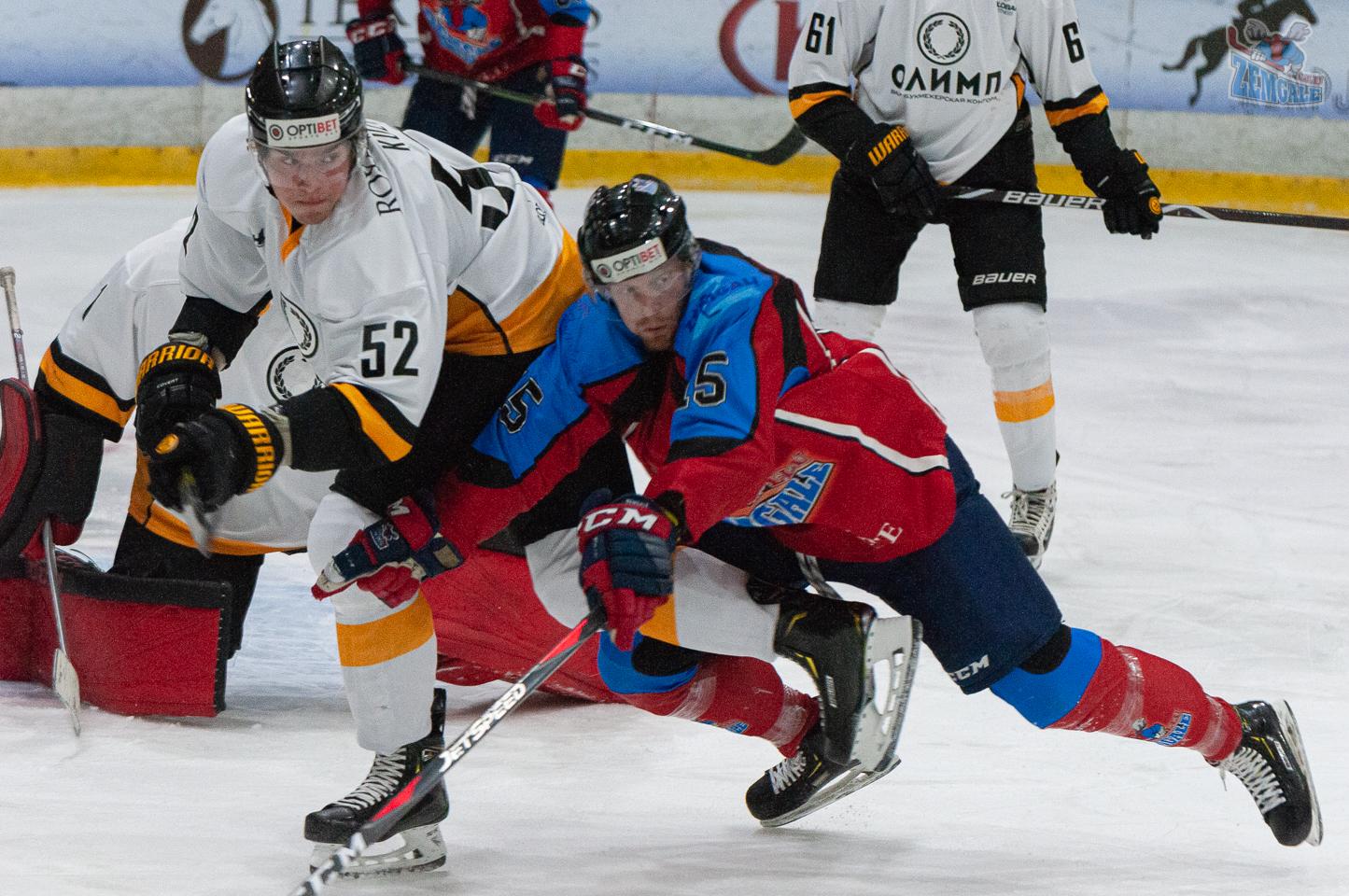 Hokeja uzbrucējs krīt virsū uz pretinieka aizsargu