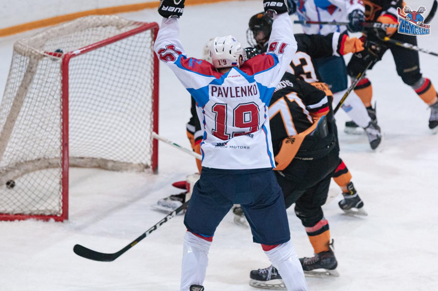 Hokeja uzbrucējs paceļ gaisā rokās pēc vārtu guvuma