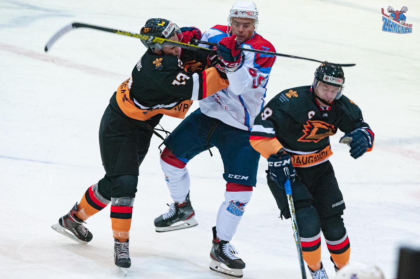 Trīs hokejisti ar nūjām sadūrās pie zilās līnijas