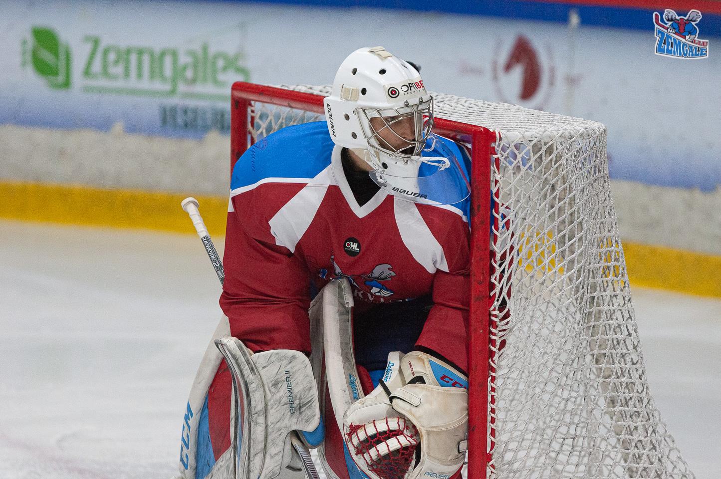 Hokeja vārtsargs stāv vārtos un vēro, kas notiek aizvārtē