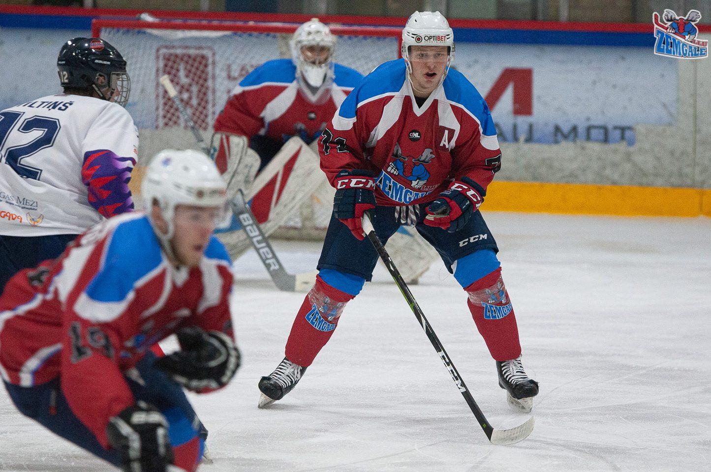 Hokeja aizsargs ar saspringtu sejas izteiksmi sagaida pretinieku uzbrucējus.