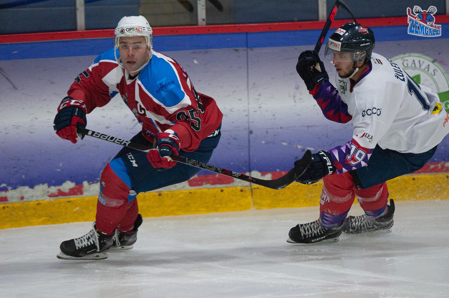 Hokejisti ar nūjām slido viens aiz otra