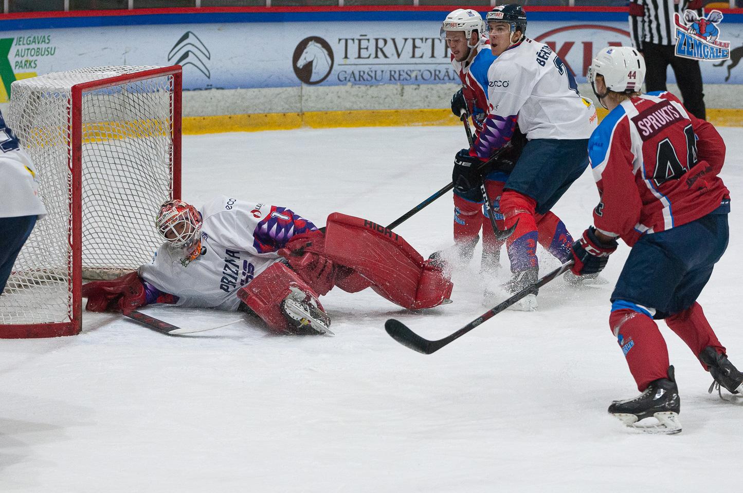 Hokeja vārtsargs guļ vārtu priekšā kamēr citi cīnās vārtu priekšā