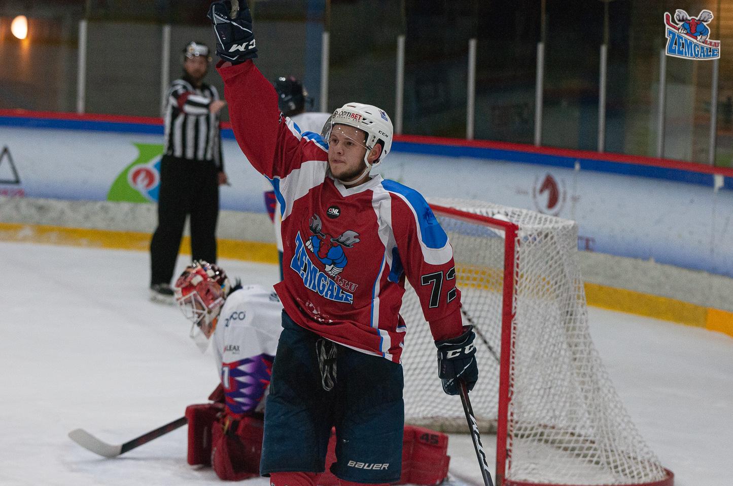 Hokejists stāv ar paceltu roku pēc vārtu guvuma