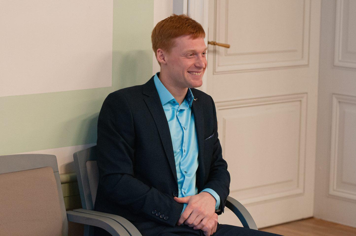 Jaunietis ar rudiem matiem un tērpts uzvalkā, sēž uz krēsla un smaida