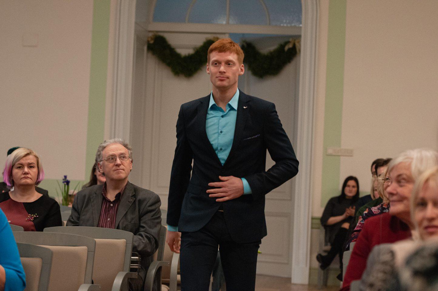 Jaunietis uzvalkā dodas caur krēslu rindu un apmeklētāji to novēro