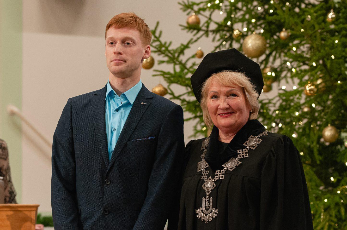 Gara auguma jaunietis stāv blakus universitātes rektorei, tērptai melnajā mantijā, cepurē un ar amata ķēdi kaklā