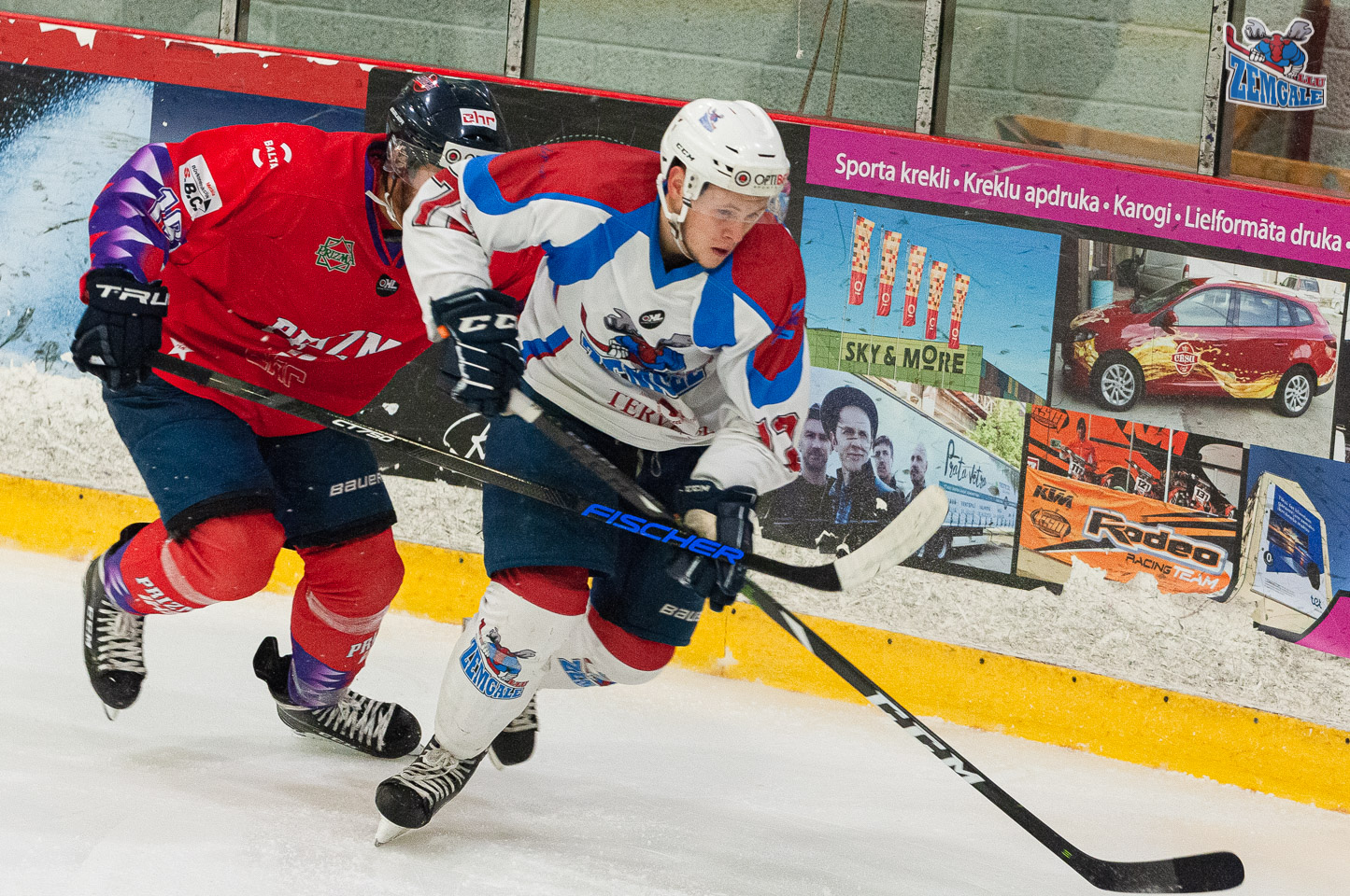 Divi hokejisti cīnās par ripu pie laukuma borta