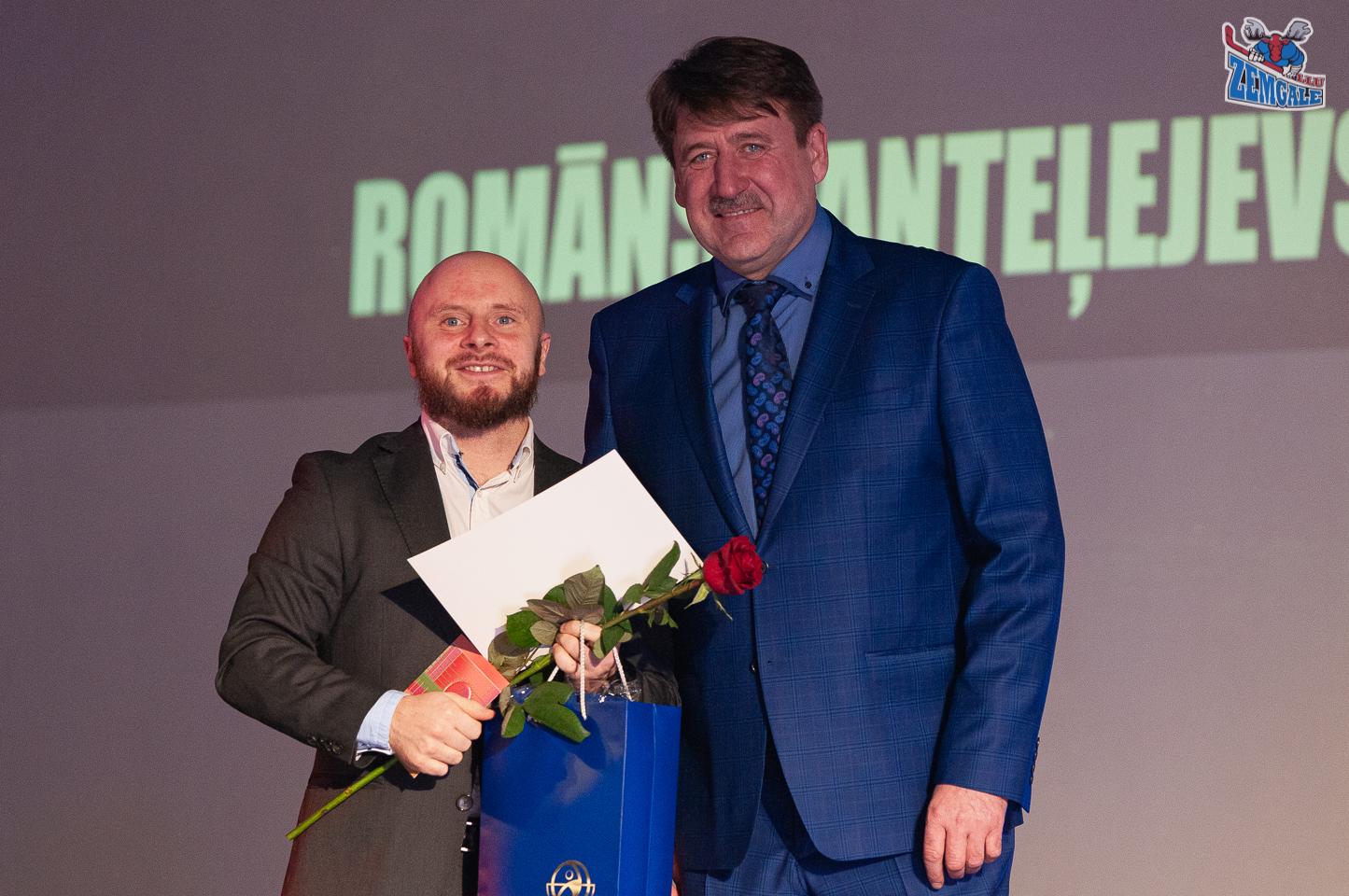 Gara un īsa auguma vīrieši ar balvām un puķēm rokās