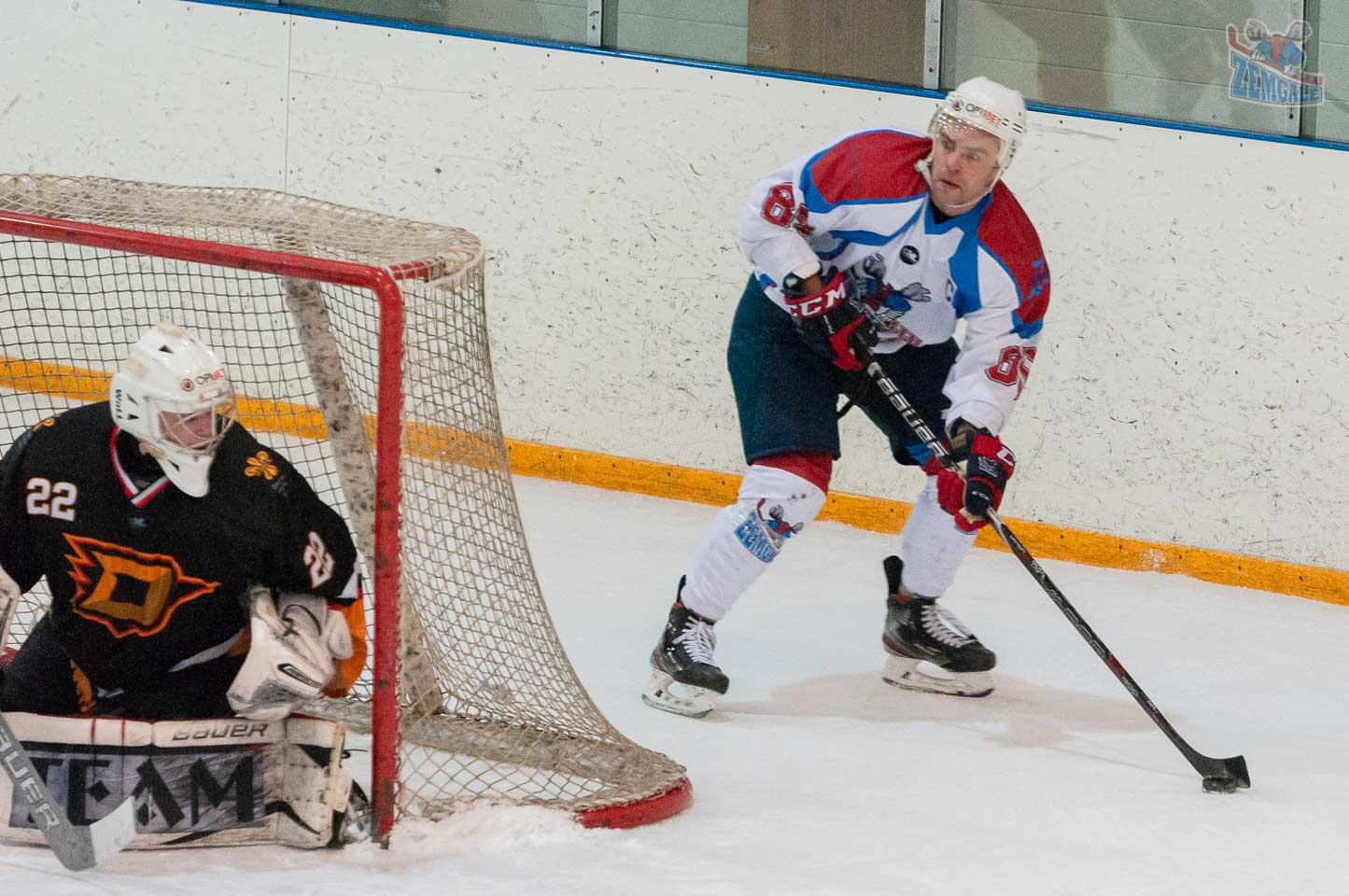 Hokejists ar ripu aiz vārtiem, kurus sargā vārtsargs