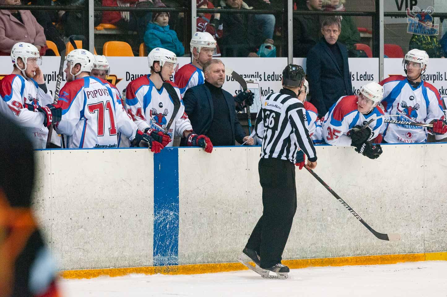 Tiesnesis skaidro savu lēmumu hokeja komandas trenerim uz rezerves soliņa
