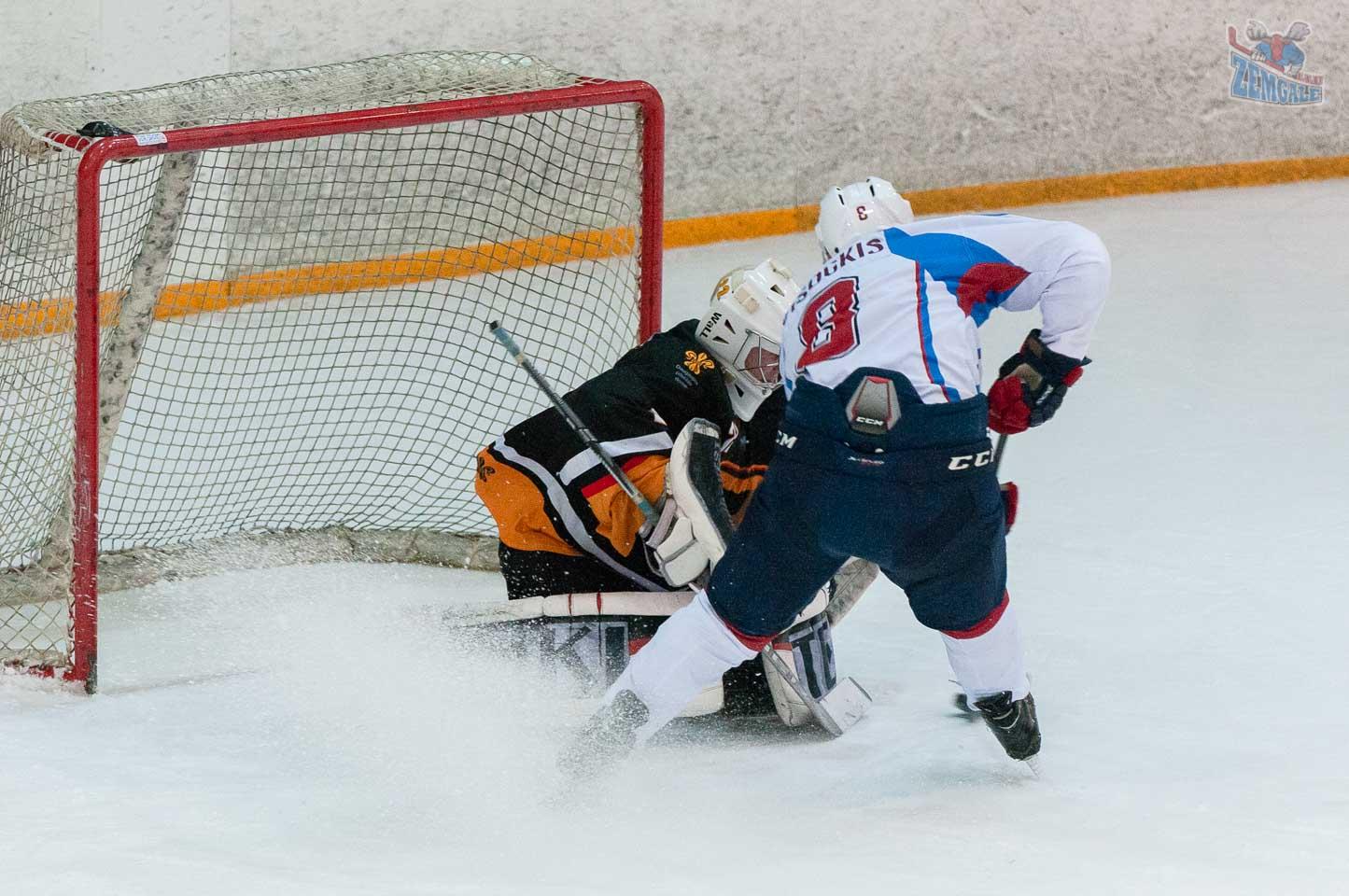 Hokeja uzbrucējs cenšas apspēlēt vārtsargu