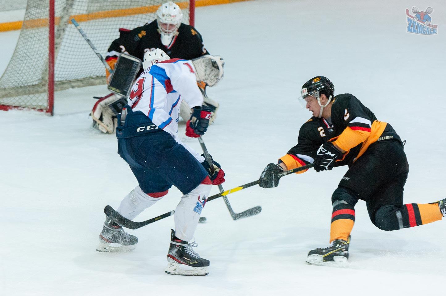 Hokeja aizsargs bloķē uzbrucēja metienu uz vārtiem