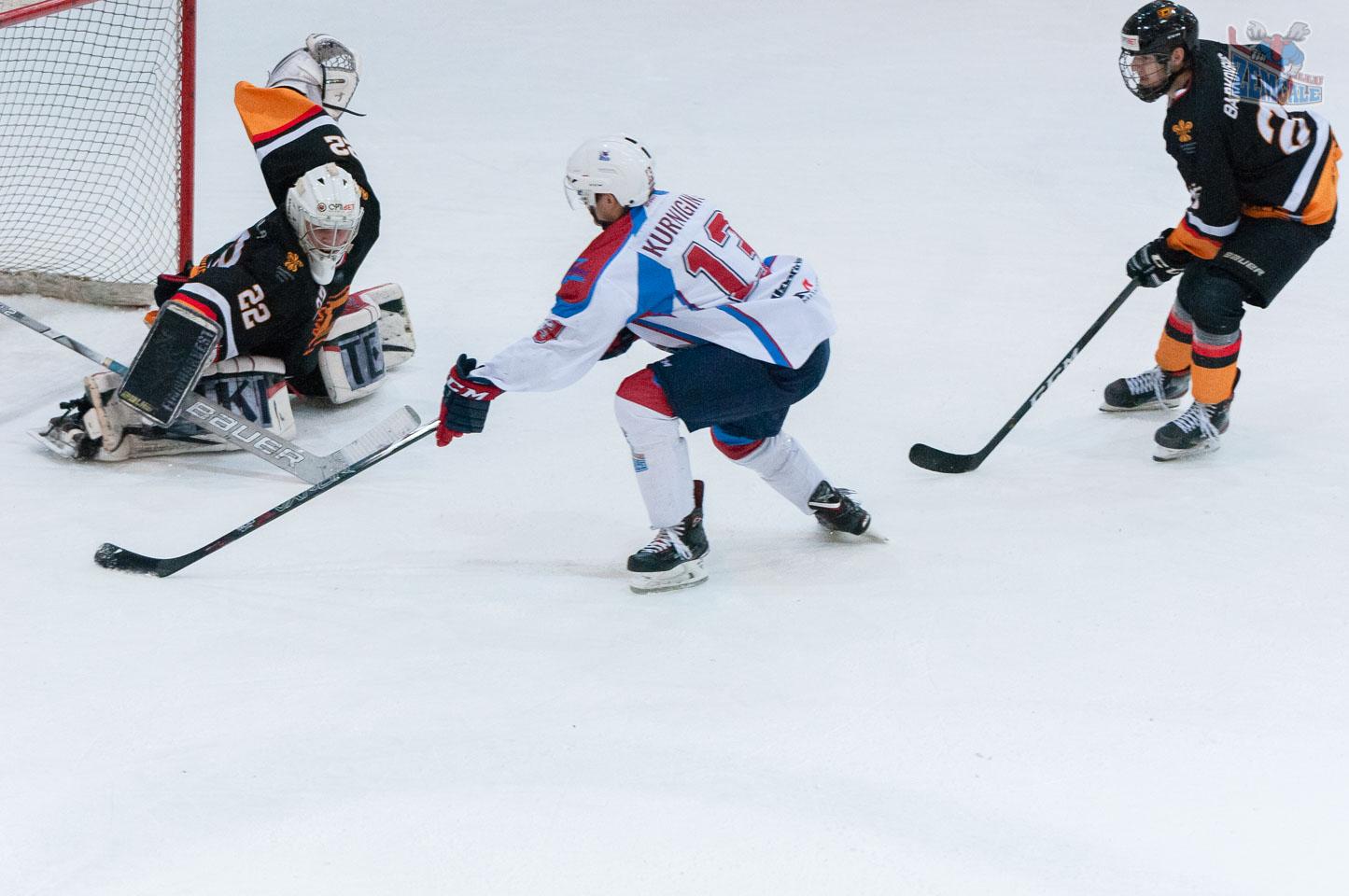 Hokeja uzbrucējs cenšas ieraidīt ripu Rauhala sargātos vārtos