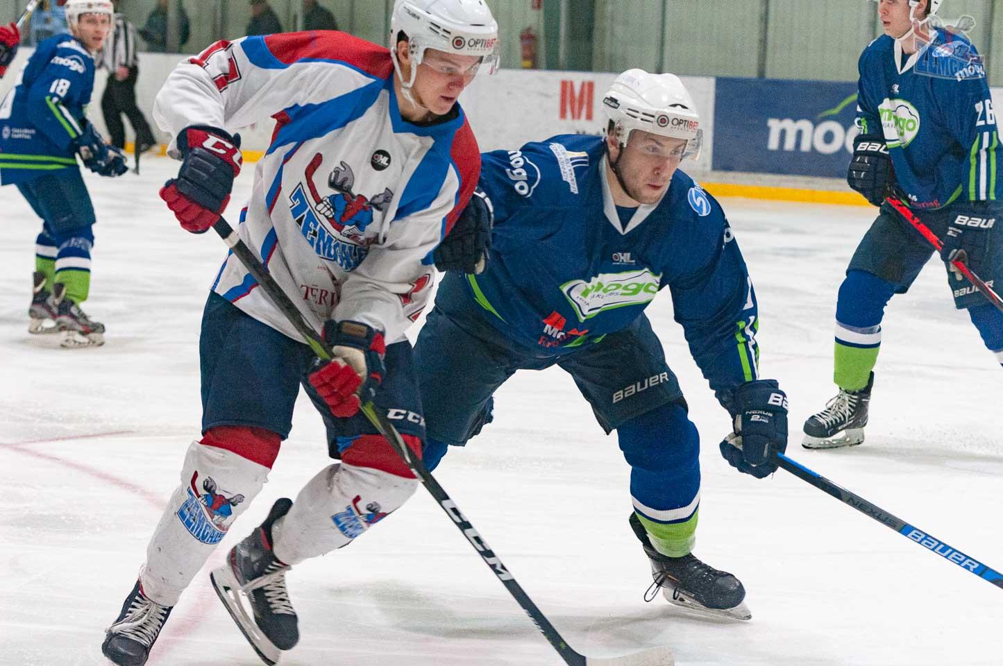 Divi hokejisti skatās uz ledus laukumu