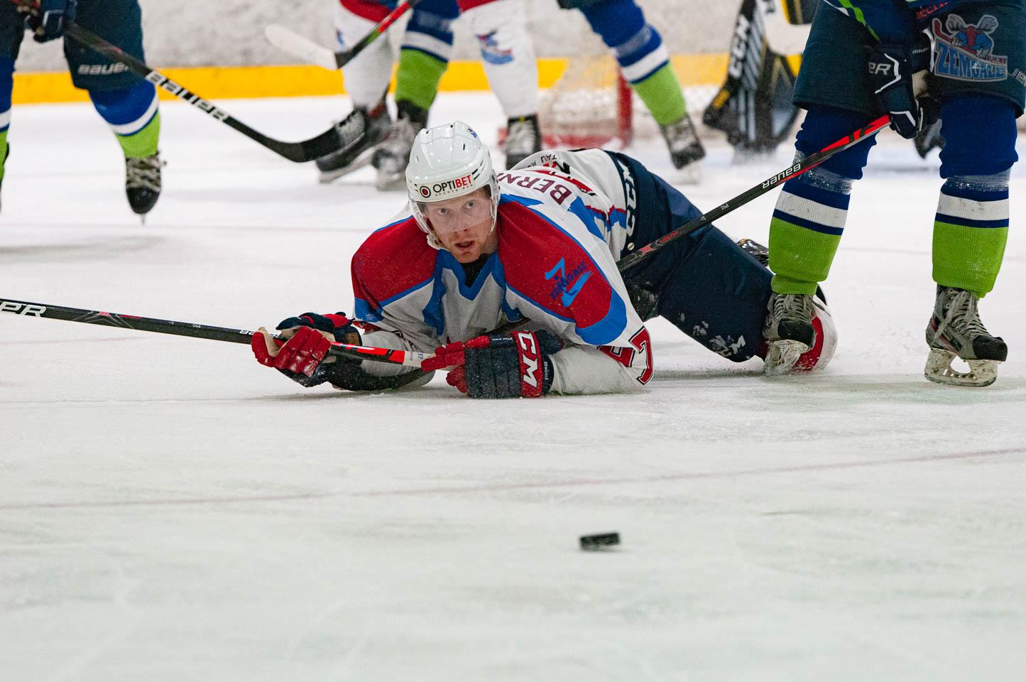 Hokejists guļ uz ledus un vēro slīdošo ripu