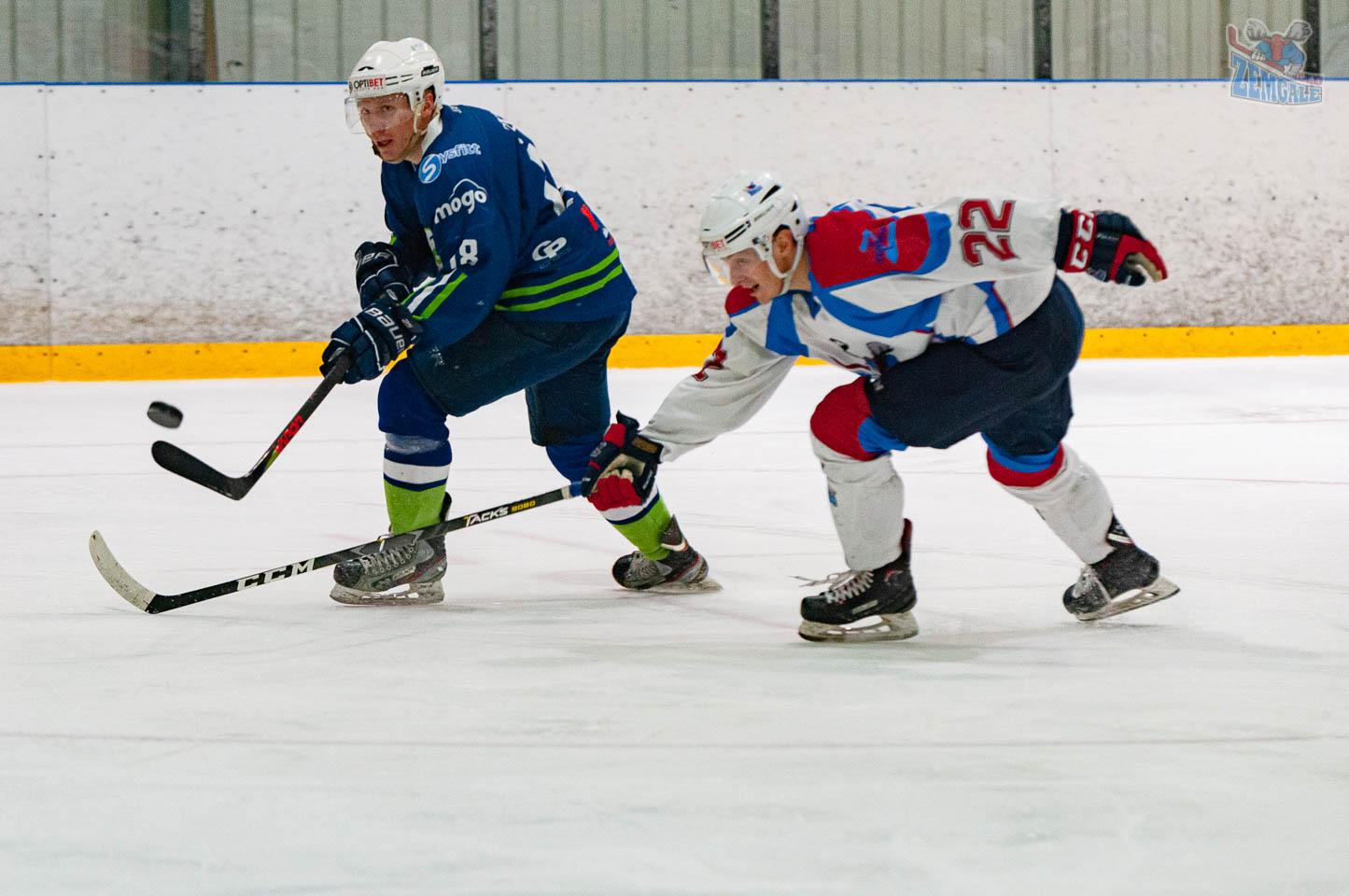 Hokejists mēģina traucēt ripas lidojumu