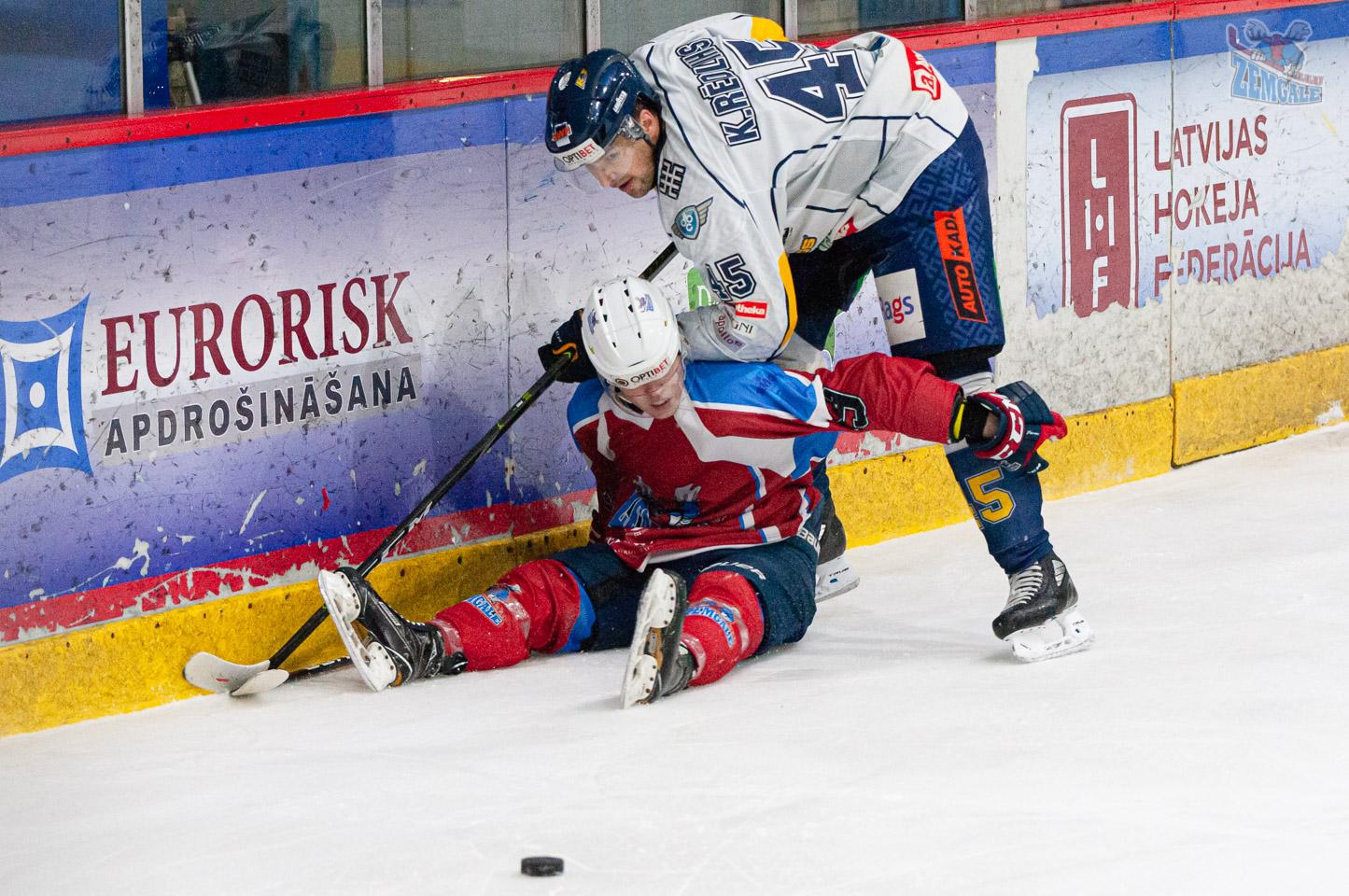 Hokejists ar elkoni spiež otru hokejistu pie ledus