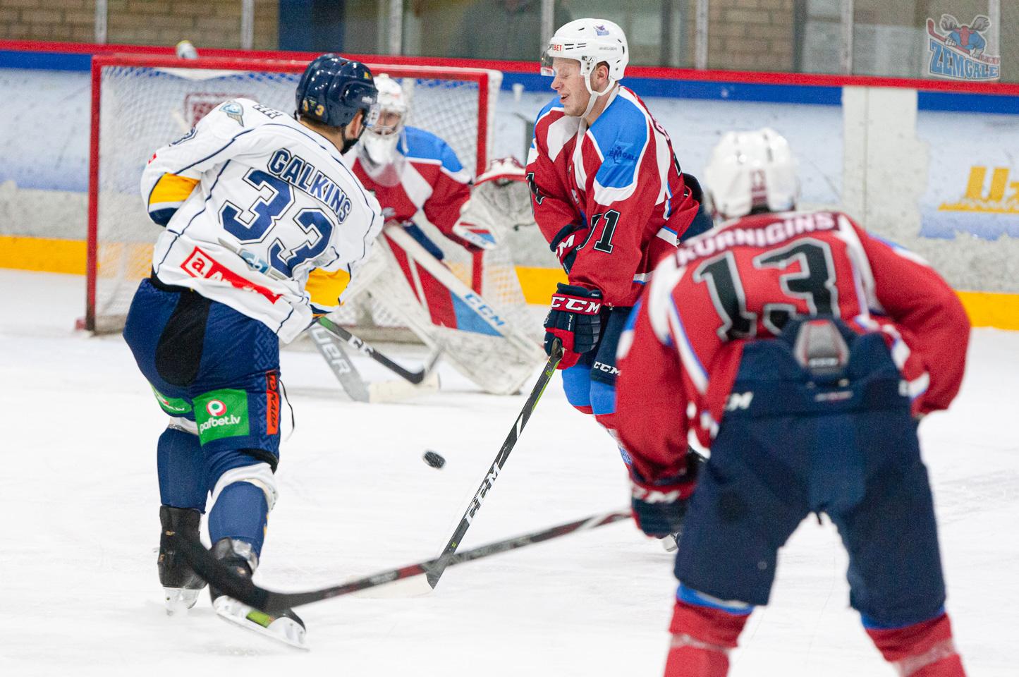 Hokejists izvairās no ripas trāpījuma, aizsargājot savu ķērmeni
