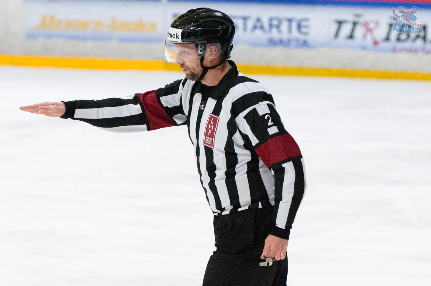 Hokeja tiesnesis norāda ar roku uz laukuma centru