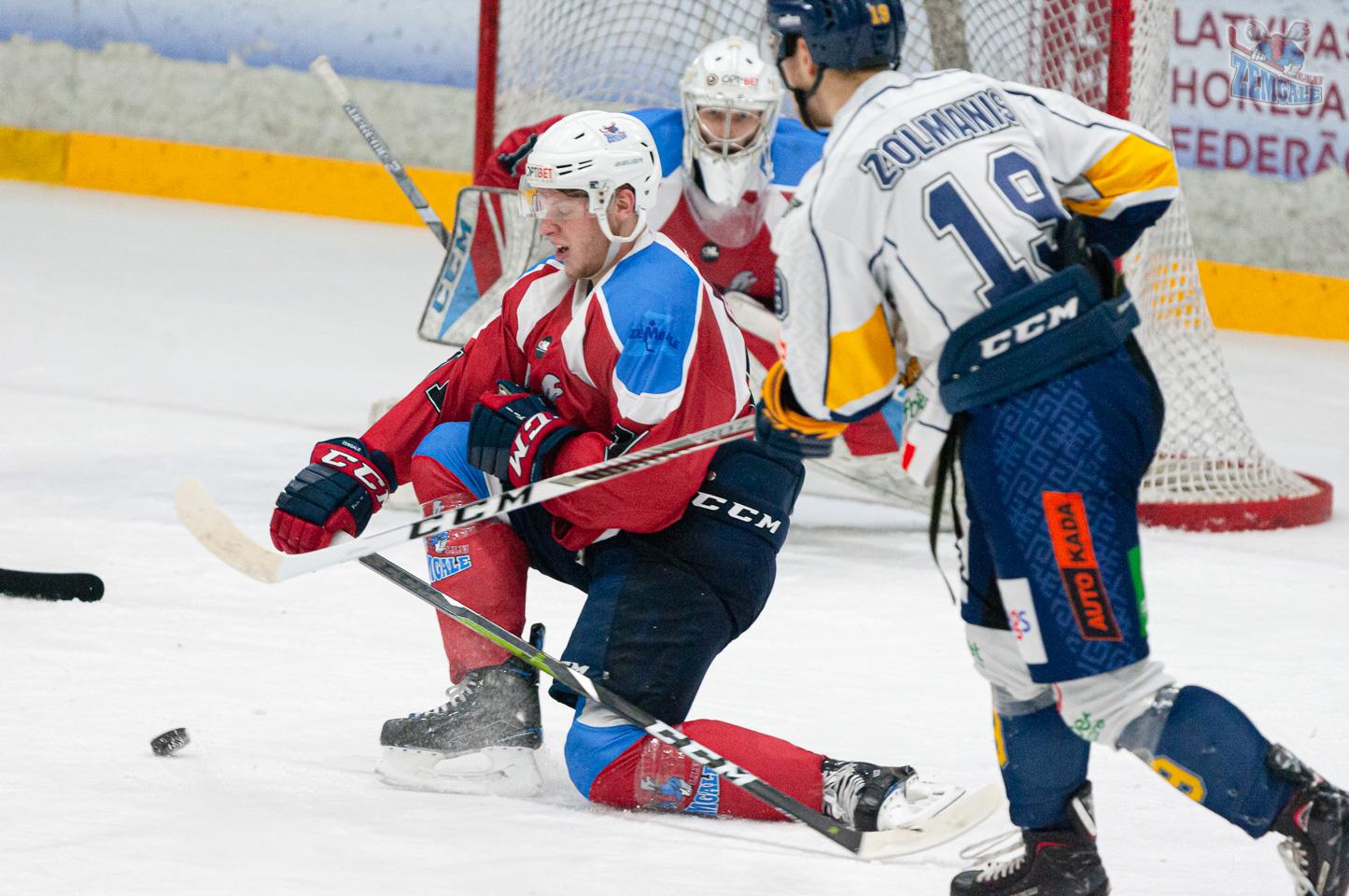 Hokeja aizsargs nosēžas uz ceļiem, lai bloķētu ripas lidojumu