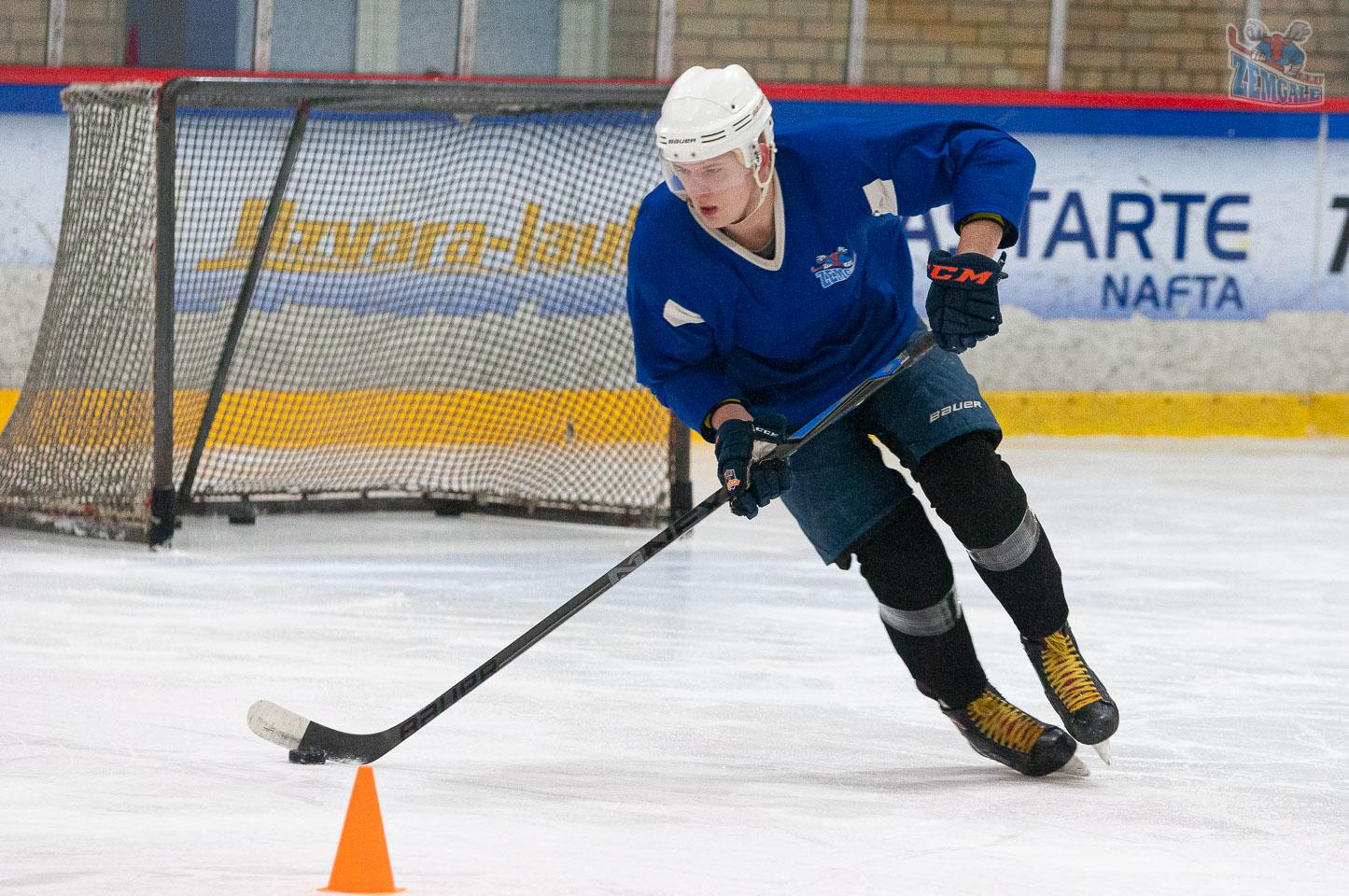 Hokejists ar ripu un nūju uz ledus. Fonā redzami vārti un konus.