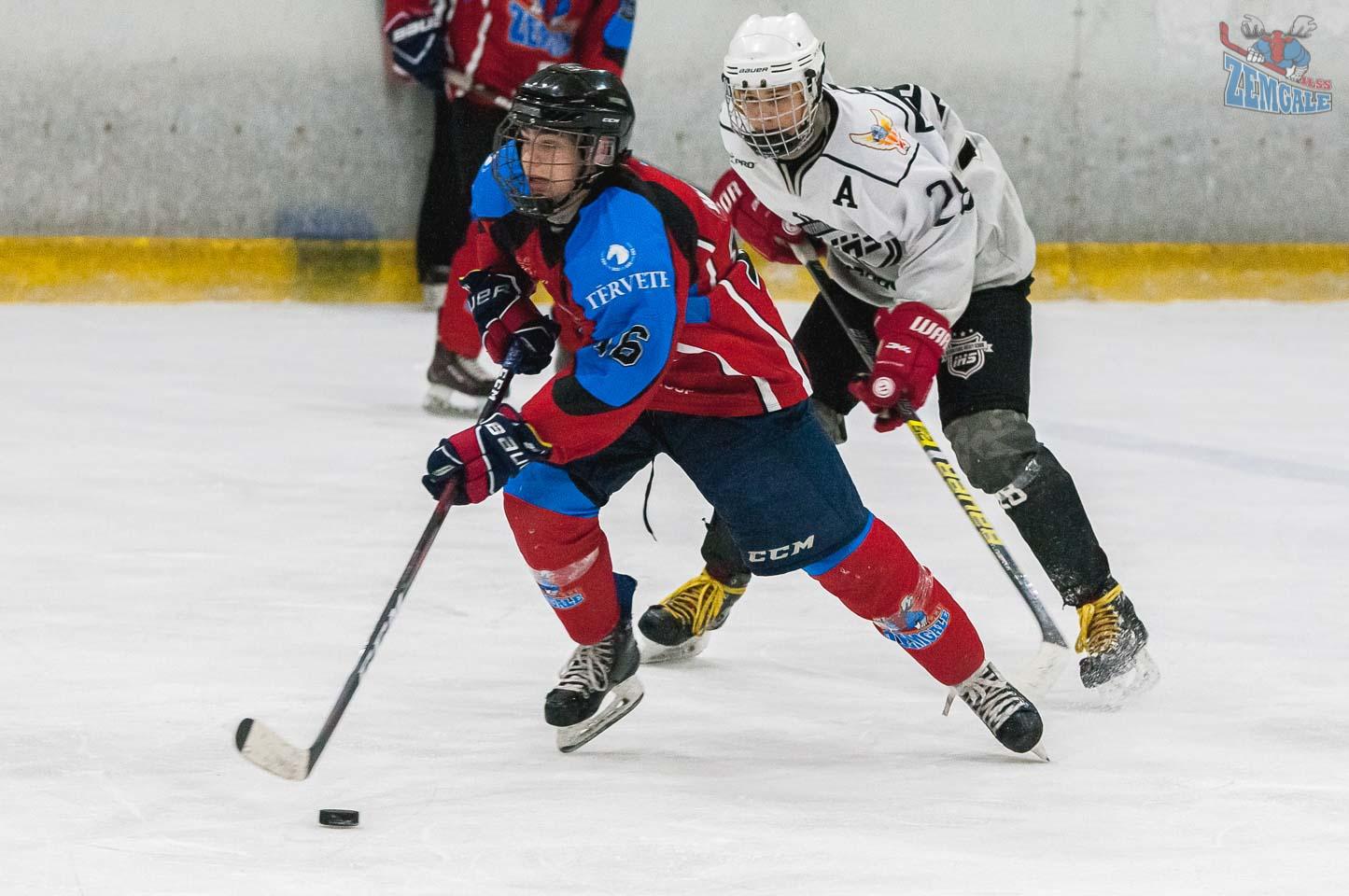 Hokejists ar ripu cenšas aizskriet no sava pretinieka