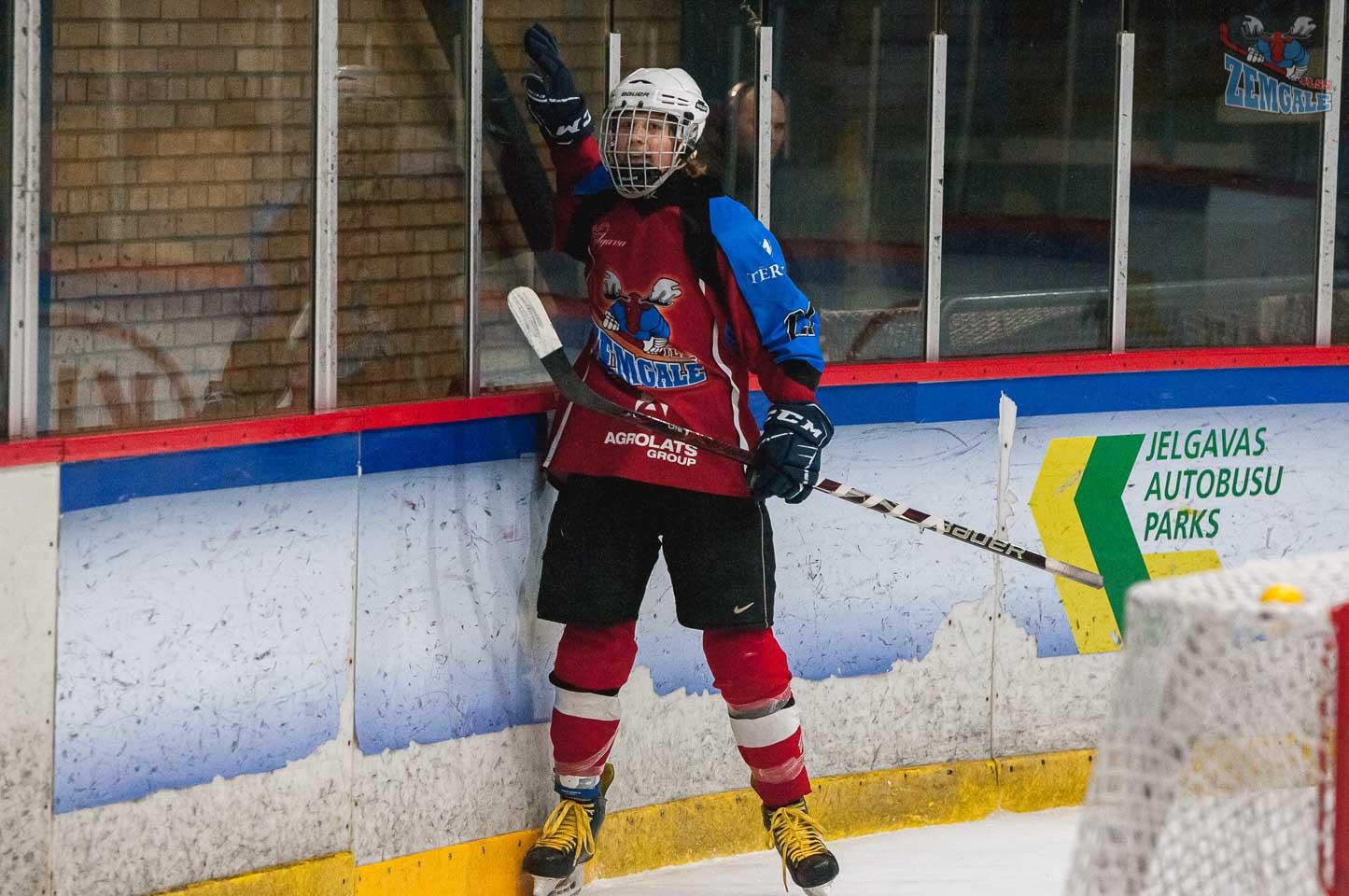 Hokeja uzbrucējs sit ar roku par stiklu, svinot gūtos vārtus