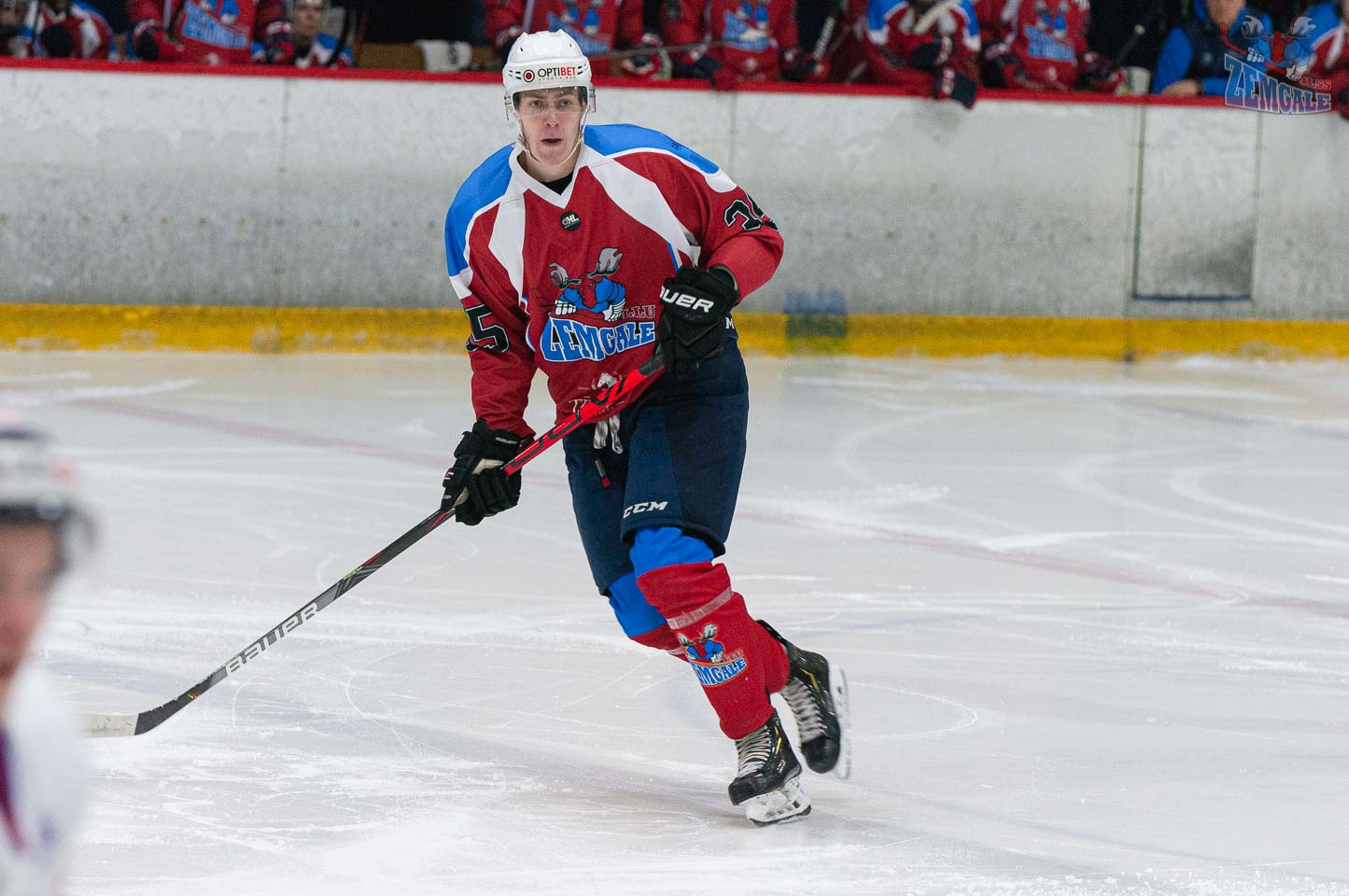 Gara auguma hokejists uz ledus slido ar nūju