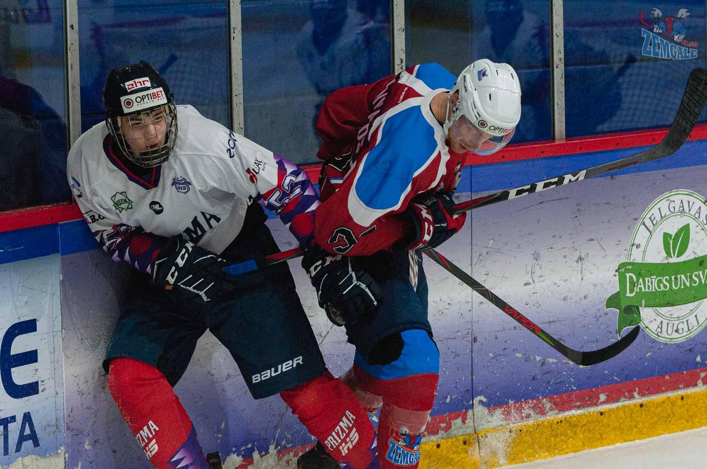 Hokejisti cīnās pie laukuma borta