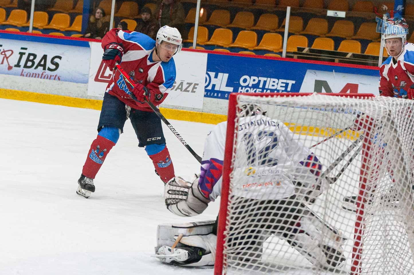 Hokejists raida ripu uz vārtiem, kurus aizsargā vārtsargs