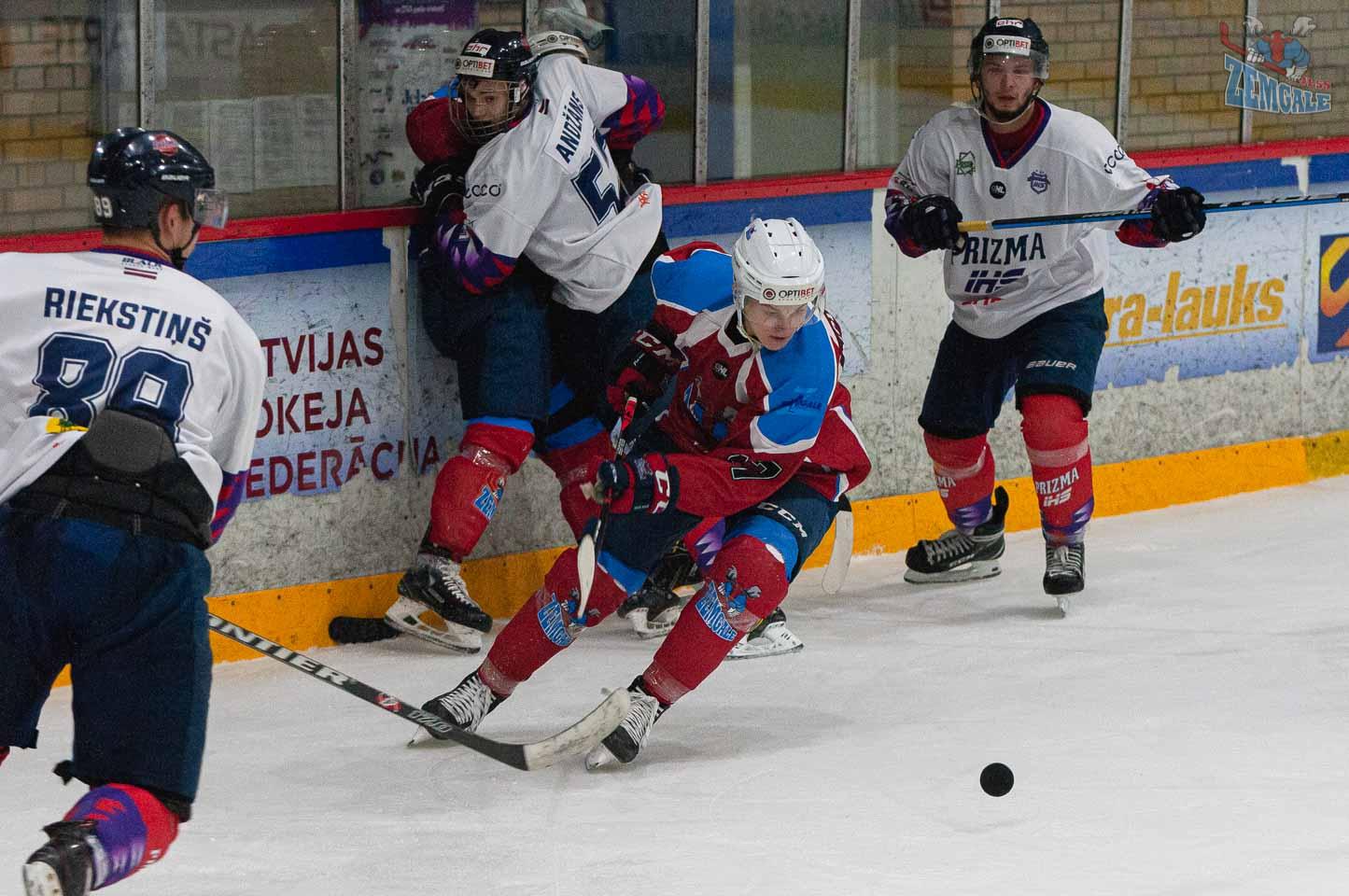 Hokejists veic virāžu, lai pārņemtu ripas kontroli starp vairākiem pretiniekiem