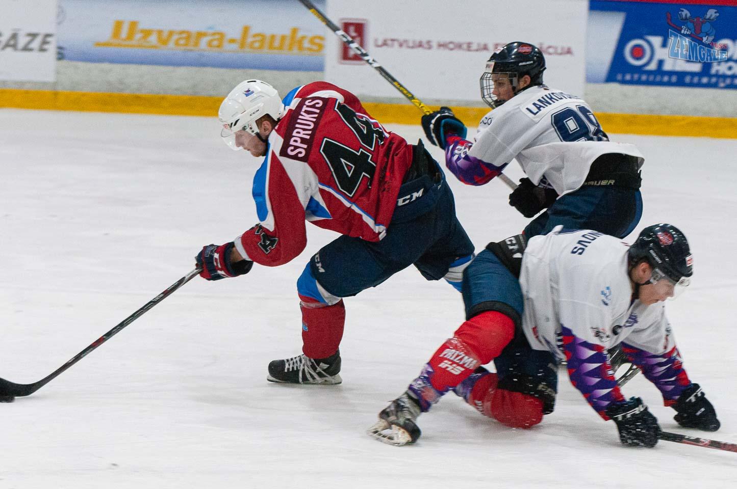 Hokeja uzbrucējs izlaužas starp diviem pretiniekiem